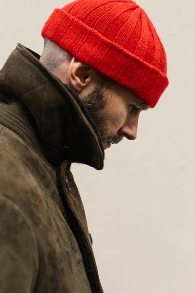 Olive shearling coat with red watch cap
