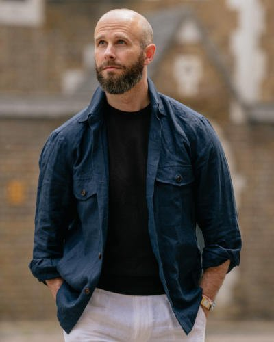 Navy overshirt over brown T-shirt, white trousers